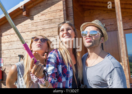 group of smiling friends taking funny selfie with smart phone - Stock Photo