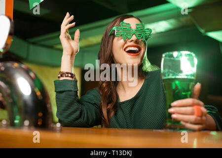 Long-haired young cute girl in a green blouse smiling brightly - Stock Photo