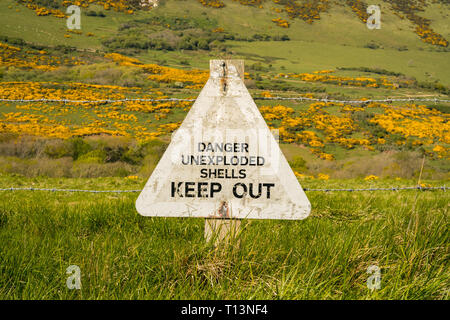 Sign: Danger unexploded shells keep out, seen on the South West Coast Path between Worbarrow Bay and Brandy Bay, Jurassic Coast, Dorset, UK - Stock Photo