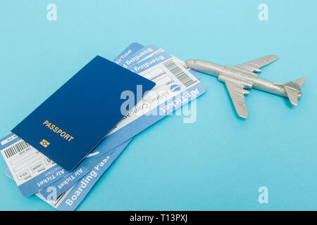 Tickets for plane and passport with model of plane on blue background. Copy space for text. - Stock Photo