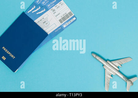 Tickets for plane and passport, dollars with model of plane on blue background. Copy space for text - Stock Photo