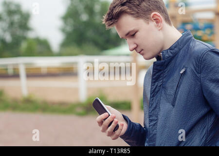 Teen holding mobile (cell) phone in hand - Stock Photo