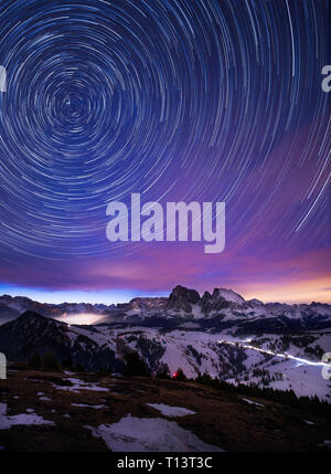 Starlit sky and first cars driving before sunrise in Mountain village Seiser Alm, Italy - Stock Photo