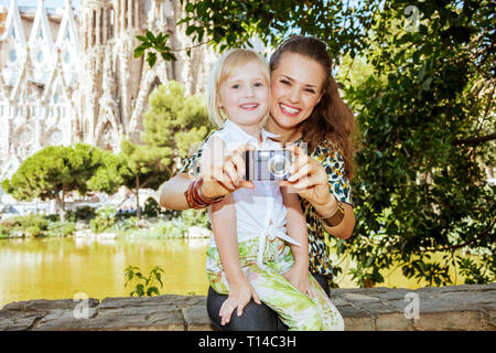Barcelona - August, 06, 2015: smiling modern mother and child tourists taking photo with digital camera in Barcelona, Spain. - Stock Photo