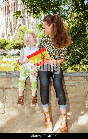 Barcelona - August, 06, 2015: smiling stylish mother and daughter tourists with Spanish flag looking at each other against La Sagrada Familia in Barce - Stock Photo