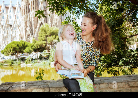 Barcelona - August, 06, 2015: smiling young mother and daughter travellers with tourist guidebook listening to an audio guide against La Sagrada Famil - Stock Photo