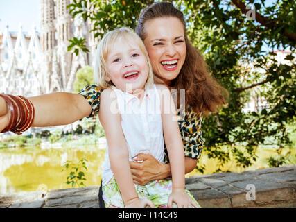 Barcelona - August, 06, 2015: smiling stylish mother and child taking selfie against La Sagrada Familia in Barcelona, Spain. - Stock Photo