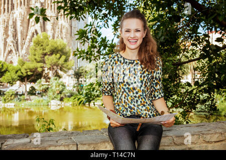 Barcelona - August, 06, 2015: smiling modern traveller woman with long brunette hair in jeans and blouse with map against La Sagrada Familia in Barcel - Stock Photo