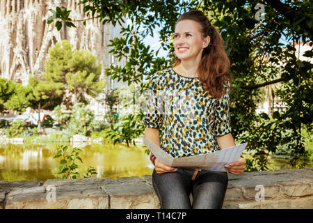 Barcelona - August, 06, 2015: smiling modern tourist woman with long brunette hair in jeans and blouse with map looking into the distance in Barcelona - Stock Photo