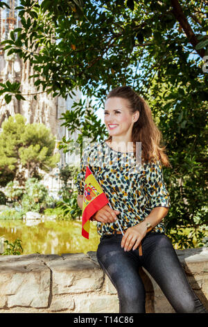 Barcelona - August, 06, 2015: smiling modern woman with long brunette hair in jeans and blouse with Spanish flag looking into the distance in Barcelon - Stock Photo