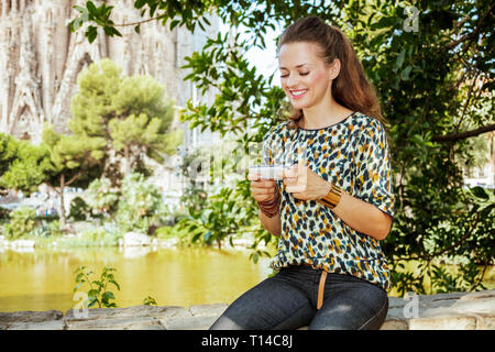Barcelona - August, 06, 2015: smiling elegant solo traveller woman with long brunette hair in jeans and blouse with smartphone using applications not  - Stock Photo