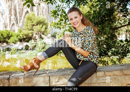 Barcelona - August, 06, 2015: smiling elegant solo traveller woman with long brunette hair in jeans and blouse with coffee cup sitting on parapet agai - Stock Photo