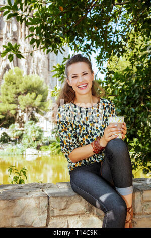 Barcelona - August, 06, 2015: smiling elegant solo tourist woman with long brunette hair in jeans and blouse with coffee cup sitting on parapet not fa - Stock Photo