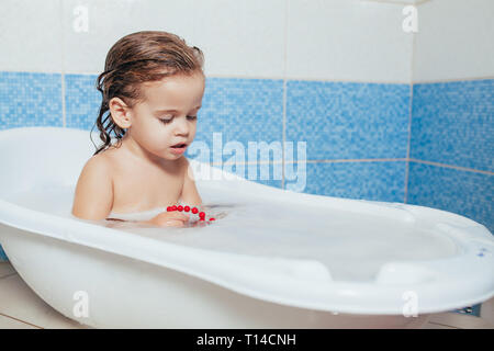 Fun cheerful happy toddler baby taking a bath playing with foam bubbles. Little child in a bathtub. Smiling kid in bathroom on blue background - Stock Photo