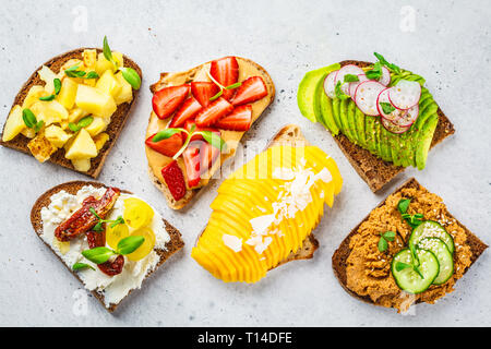 Different types of sandwiches with mango, strawberry, tofu pate, avocado, potatoes and ricotta on a white background. - Stock Photo