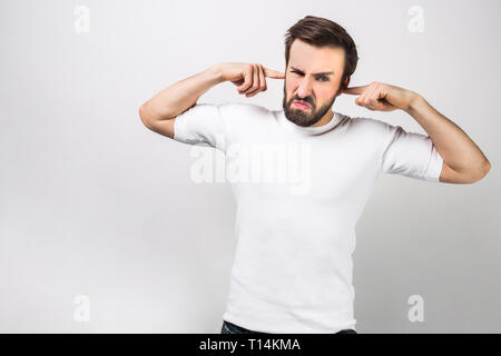 Serious and angry man that doesn't want to hear anything. He is closing his ears with his fingers. Isolated on white background - Stock Photo