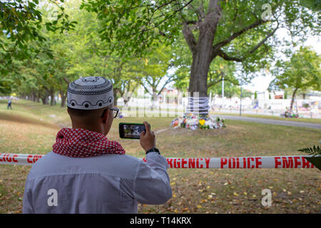 Christchurch, Canterbury, New Zealand, March 22 2019: A Muslim man takes photos of the floral tributes left in front of the Masij Al Noor in sympathy - Stock Photo