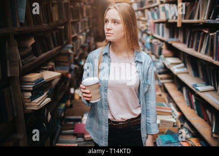 Attractive and nice girl is standing among big and long bookshelfs with old books. She is holding a cup of coffe in her hand and looking to the shelf. - Stock Photo