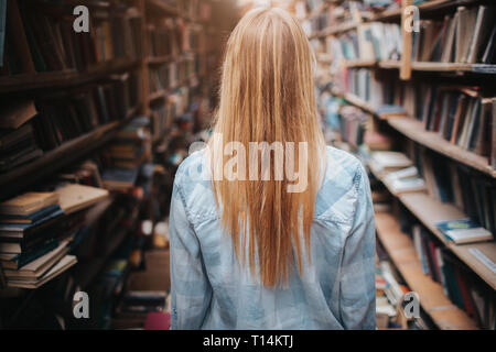 A picture og girl walking among bookshelfs with new and olb books. There is a mess everywhere in the room. She ir making a reseach - Stock Photo