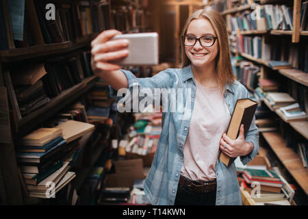 A cute picture of a blonde girl taking selfie. She is looking to the phone and smiling. This girls is in a big public library - Stock Photo