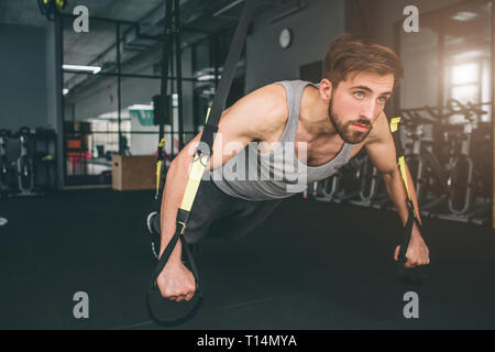 Close up of a strong and powerful man doing some stretching using trx loops for that. He is doing some pushups and trying to stay balanced at the same - Stock Photo