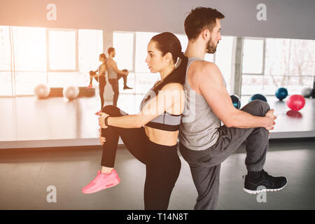 A picture of man and woman standing back to back and pulling up one leg. They are trying to keep the balace of bodies on one hand. Close up. Cut view. - Stock Photo