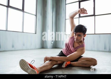 asian young man doing abdominal stretching before workout - Stock Photo