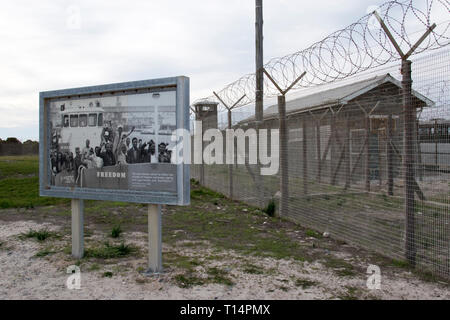 A barbed wire fence and prison block at Robben Island, where Nelson Mandela was imprisoned during apartheid, Cape Town, South Africa. - Stock Photo