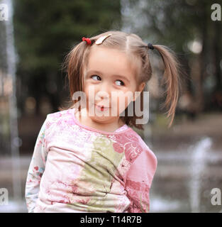 pretty little girl on the background of the city fountain - Stock Photo
