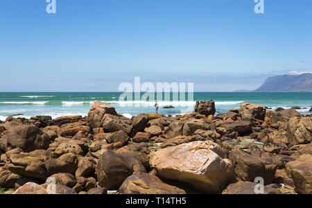 a lone sea fisherman on the rocks at the coast with his rod and line hoping to catch a fish on a beautiful Summer day with blue sky - Stock Photo
