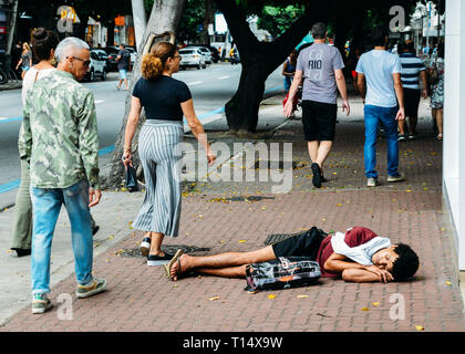 Rio de Janeiro, Brazil, March 23, 2019: Homeless young man sleeping rough while pedestrians walk next to him on busy pedestrian sidewalk in the wealth - Stock Photo