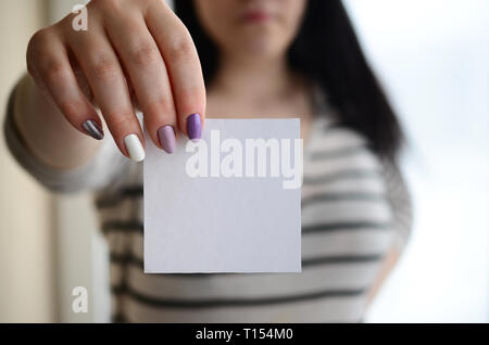 Young sad girl shows a white sticker. Caucasian brunette holding a blank sheet of paper as a template for your text