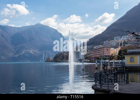 Lugano, Switzerland - March 10, 2019: A view of central Lugano with lake and fountain - Stock Photo