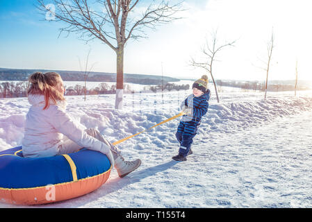A little boy pulls a tubing on him, which mom sits. Happy play in the winter outside on a frosty day. Against the backdrop of snow and snow drifts. - Stock Photo