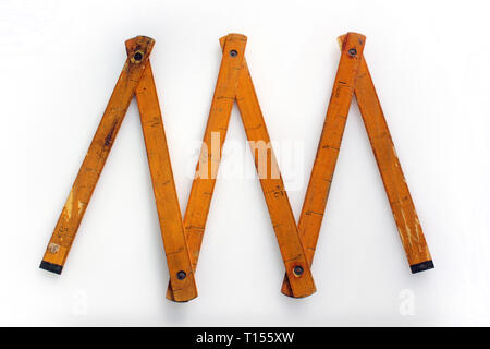 Vintage wooden folding ruler isolated on a white background.isolated on white background, close-up - Stock Photo