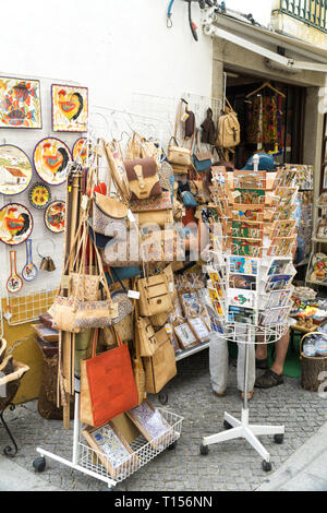 EVORA, PORTUGAL: Undefined tourists shopping in the main street of the Evora. A typical souvenir from Evora is cork products: bags; valets, hats etc. - Stock Photo