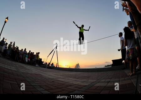 Male street performer balancing on tightrope while juggling, entertain crowds, Mallory Square Sunset Celebration, Key West, Florida Keys, Florida, USA - Stock Photo