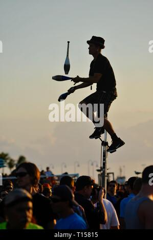 Male street performer pedaling on a unicycle while juggling, entertaining crowds, at Mallory Square on Key West, Florida Keys, Florida, USA - Stock Photo