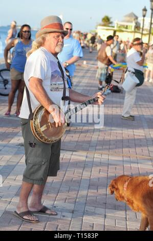 Male musician street performer playing banjo for crowds of tourists at Mallory Square on Key West, Florida Keys, Florida, USA - Stock Photo