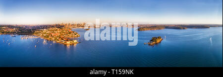 Wealthy suburbs of Sydney on shores of Sydney harbour with city CBD high-rise towers and the Harbour bridge on the horizon is elevated aerial wide pan - Stock Photo