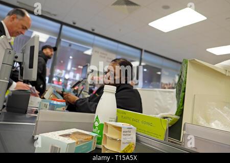 Waitrose supermarket checkout counter and food kefir on conveyor belt, older female worker working at till serving customer London UK  KATHY  DEWITT - Stock Photo