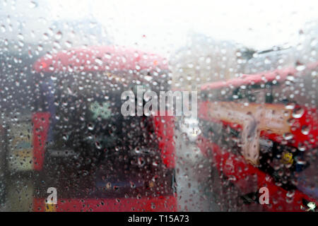 A view of double decker red buses in traffic view from top of bus interior raindrops on window on rainy day in London England UK  KATHY DEWITT - Stock Photo