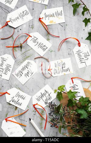 A multicultural Christmas: ready to use hand made gift tags with Merry Christmas written in multiple languages - Stock Photo
