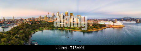 Early morning sunrise panorama of Sydney city CBD landmarks on shores of Sydney harbour with reflection in still waters and high-rise towers against s - Stock Photo