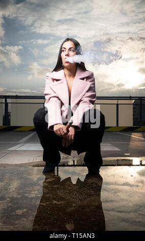 Portrait of fashionable young woman smoking electronic cigarette on parking level - Stock Photo