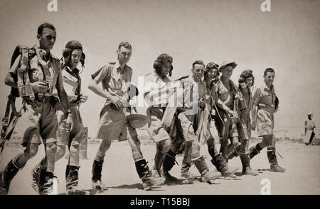 Bomber crews in hot weather outfits walking out to their aircraft prior to a raid over the African desert. The North African Campaign of the Second World War took place from June 1940 to May 1943 and included campaigns fought in the Libyan and Egyptian deserts (Western Desert Campaign, also known as the Desert War) and in Morocco and Algeria (Operation Torch), as well as Tunisia (Tunisia Campaign). - Stock Photo