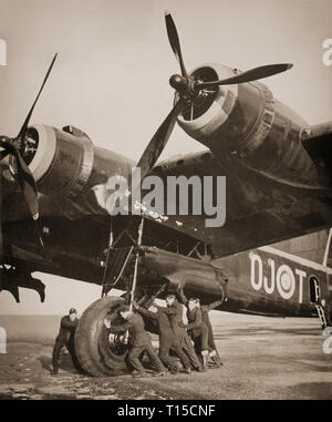 Ground crew moving a 20 ton Short Stirling, British heavy bomber of the Second World War. The first four-engined bomber to be introduced into Royal Air Force squadron service in early 1941. The Stirling was relegated to second line duties from late 1943, due to the increasing availability of the more capable Handley Page Halifax and Avro Lancaster, which took over the strategic bombing of Germany. - Stock Photo