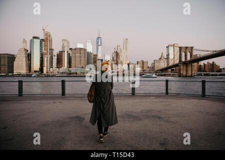USA, New York, New York City, Brooklyn Bridge, Female tourist at East River - Stock Photo