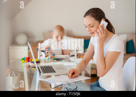 Mother working and little daughter playing at table at home - Stock Photo