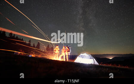 Night camping in the mountains. Young friends hikers having a rest together around bonfire near tourist tent at night. On background forest and beauti - Stock Photo